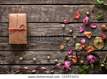 Craft gift box with rose petals and dried flowers on old wooden plates. Lovely holiday background. - stock photo