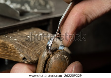 Craft jewelery making.  Repairing ring by inlaid tight gem. - stock photo