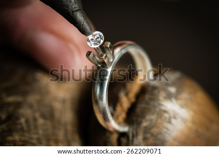 Craft jewelery making. Ring repairing. Putting the diamond on the ring. Macro shot. - stock photo