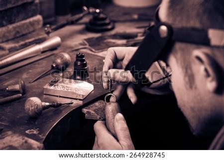 Craft jewelery making.  Ring repairing. Putting the diamond on the ring. Monochrome cream tone. Black and white photography. - stock photo