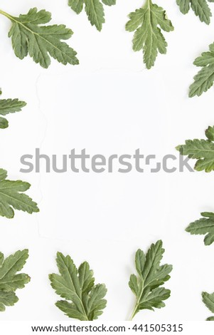 Craft paper card and green leaves on white background. Overhead view. Flat lay, top view.