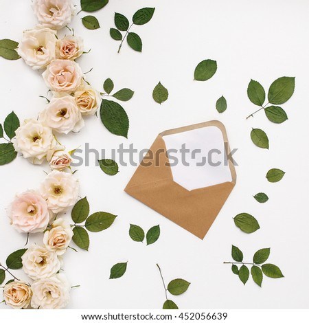 Craft paper envelop with white card and pink roses. Flat lay, top view, isolated on white background - stock photo
