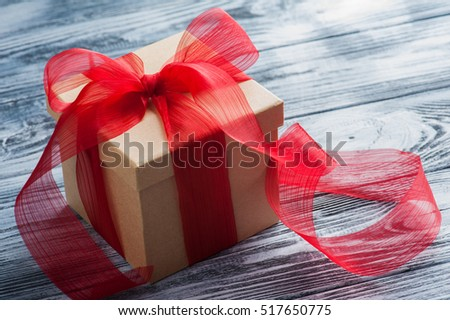 Craft paper gift box with red bow on old wooden table. Place for text