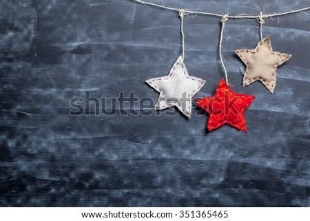 Craft stars on textured empty chalkboard background