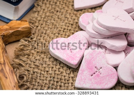 Crafted pink heart shape with wooden cross on sackcloth for religion symbol background - stock photo