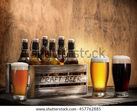 Crafting beer in bottles and glasses. On top of a wooden background.