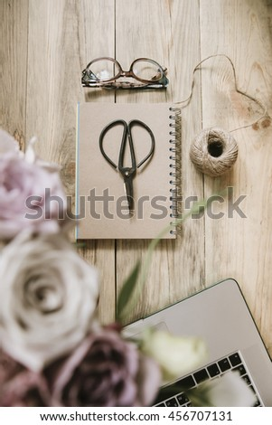 Crafting scissors, glasses, cardboard notebook, twine,laptop and flower bouquet on the old rustic table background