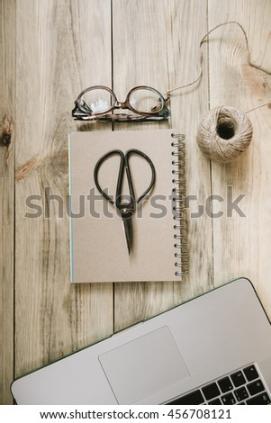Crafting scissors,glasses, cardboard notebook, twine, laptop on the old rustic table background - stock photo