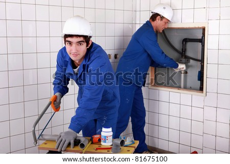 craftsman and apprentice working together - stock photo