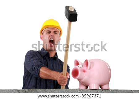 craftsman breaking a pig bank with a hammer - stock photo