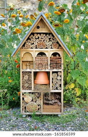 Craftsman built insect hotel decorative wood house with compartments and natural components refuge made to protect and promote ladybugs and butterflies hibernation as useful garden pests  - stock photo