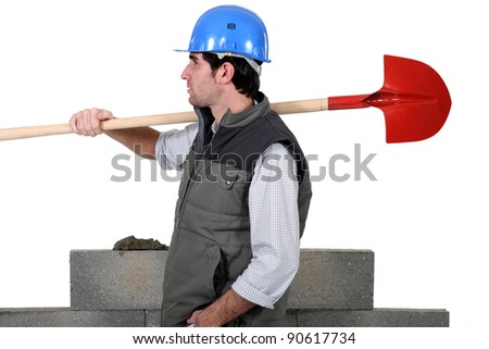 craftsman carrying a shovel on his shoulder - stock photo