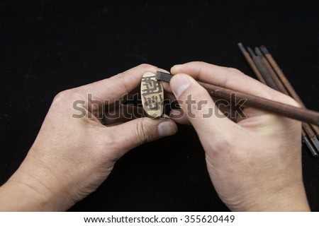 Craftsman carving a stone seal Chinese
