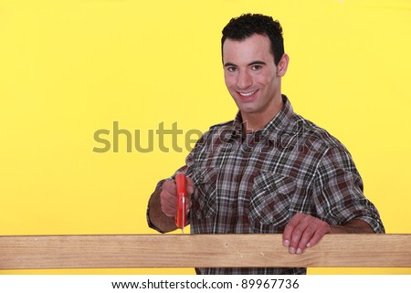 craftsman cutting a wooden board with a saw - stock photo