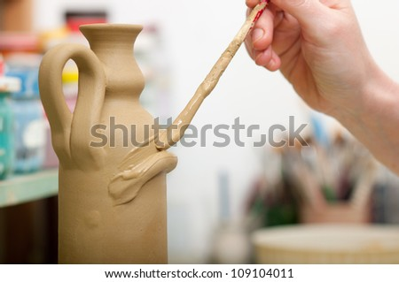 Craftsman decorating with brush bottle made of fresh clay in pottery workshop. Shallow depth of field. Focus on brush tip. - stock photo