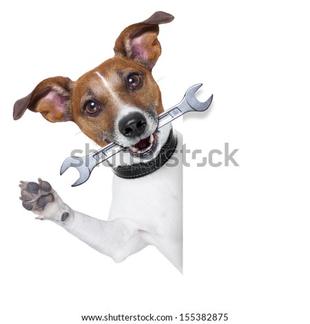 craftsman dog with spanner wrench in mouth beside a white blank banner - stock photo