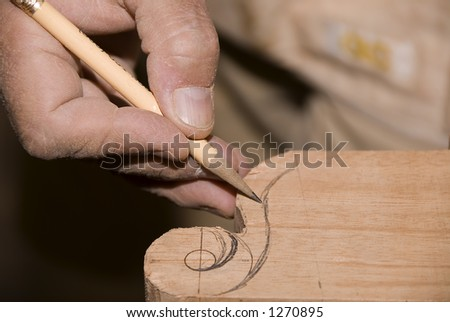 Craftsman drawing a design on wood - stock photo