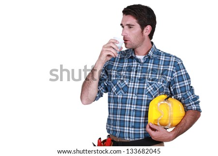 craftsman having cup of coffee hard hat in hand - stock photo