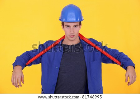 craftsman holding a huge spanner behind his neck