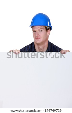 craftsman holding a poster and grimacing - stock photo