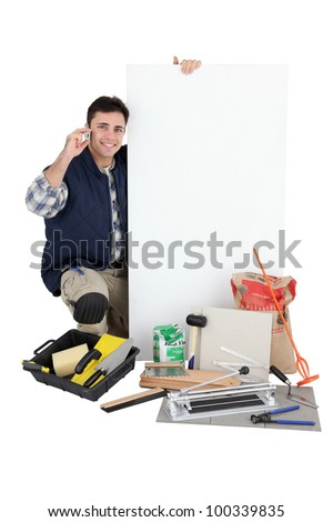 craftsman holding an ad board and talking on the phone - stock photo