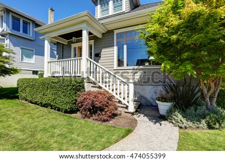 Craftsman house porch with square columns and staircase. Concrete walkway and green grass with trimmed bushes. Northwest, USA