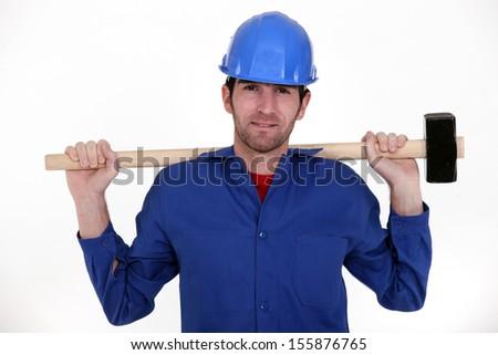 craftsman in blue overalls holding huge hammer - stock photo