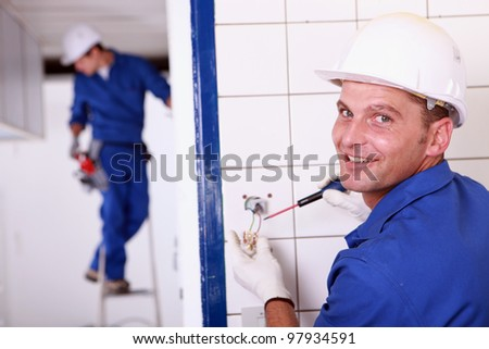 craftsman installing an electricity socket - stock photo