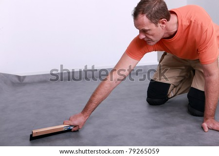 craftsman leveling the floor - stock photo