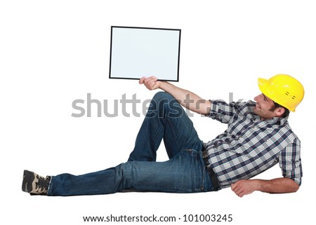craftsman lying and holding a blank board - stock photo