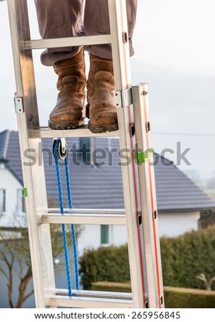 craftsman on a ladder at the house, icon crafts, home improvement, safety, career - stock photo