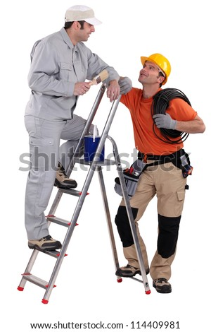 craftsman painter on a ladder speaking with a colleague - stock photo