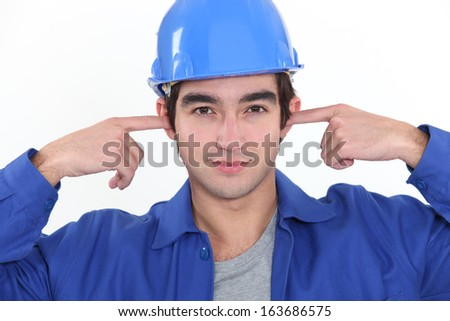 craftsman plugging his ears - stock photo