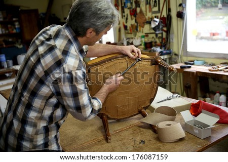 Craftsman repairing antique armchair in workshop - stock photo