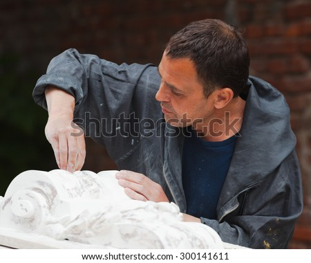 craftsman restorer working with gypsum model - stock photo