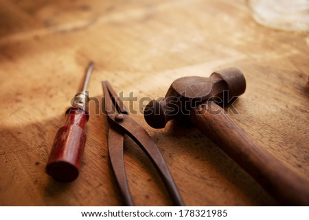 Craftsman's tools. Old and well used hammer, pliers and screw driver on a old wooden desk. With warm lighting.  - stock photo