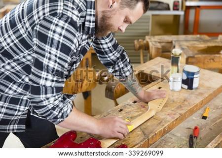 Craftsman sanding guitar neck in wood at workshop - stock photo