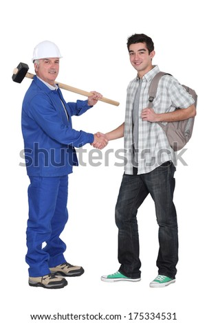 Craftsman shaking hands with apprentice - stock photo