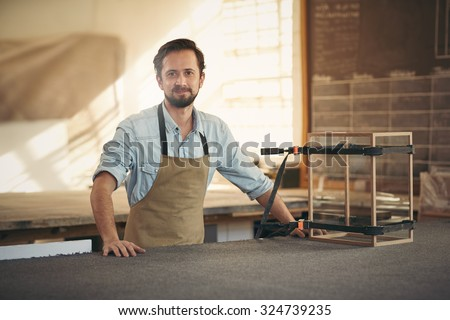 Craftsman smiling at the camera while standing proudly in his workshop alongside a wood and glass display case that he is making with care - stock photo