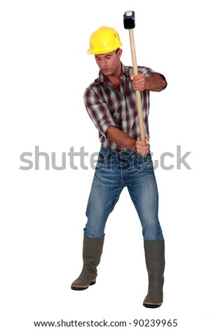 craftsman striking with a huge hammer - stock photo