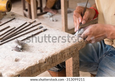 Craftsman using a tool on a marble to carve a statue elephant - stock photo