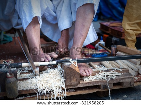craftsman using his feet to carve wood