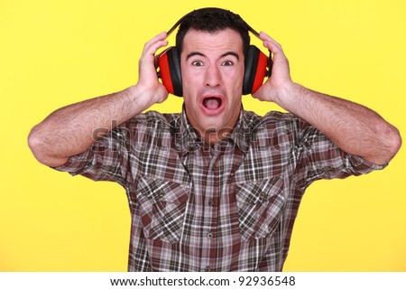 craftsman wearing headphones can't stand the noise - stock photo