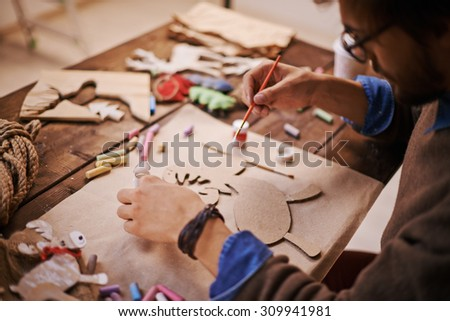Craftsman with paintbrush painting paper deer before Christmas - stock photo