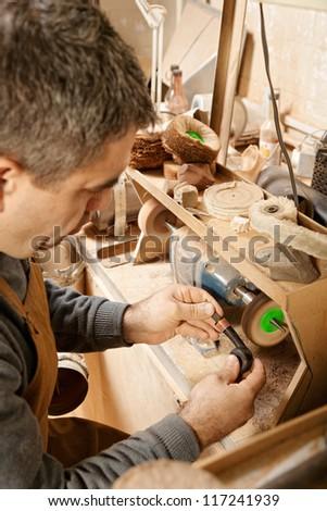 Craftsman working on grinder finishing smoking pipe - stock photo