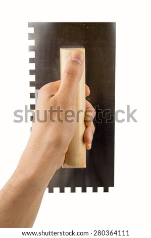 craftsperson holding the trowel over white wall - stock photo