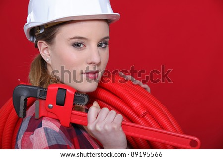 craftswoman holding a pipe hose and a spanner - stock photo