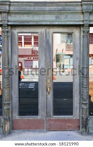 Crafty door with wood carving and windows with street reflection