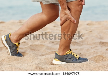 Cramps in leg calves or sprain calf on triathlete runner. Sports injury concept with running man. - stock photo