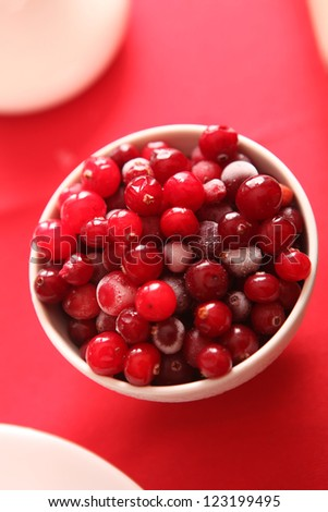 cranberries in a bowl on red background - stock photo